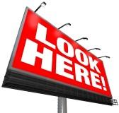 12583632-le-parole-look-here-su-uno-sfondo-rosso-su-un-grande-cartellone-esterno-per-attirare-l-attenzione-e-